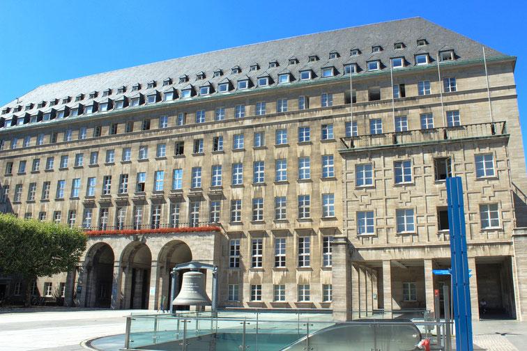 Bochumer Rathaus an einem sonnigen Tag, davor Glocke der Weltausstellung 1867 in Paris; Kurtz Privatdetektei Bochum