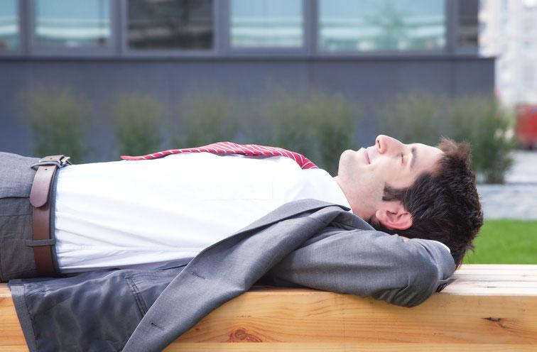Mann im Anzug schläft grinsend auf einer Holzbank; Kurtz Detektei Bochum, Mitarbeiterüberwachung durch Detektive