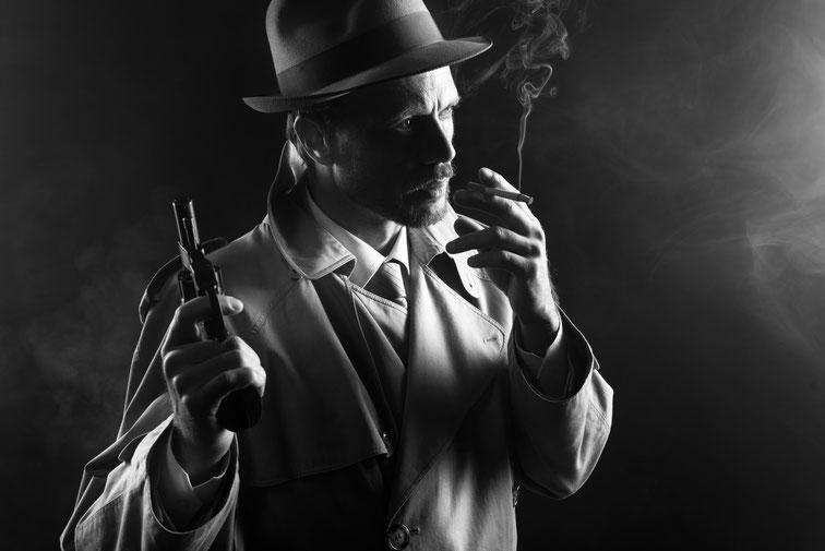Mann in schwarz-weiß, Trenchcoat, Hut, Pistole in der einen Hand, Zigarette in der anderen; Detektive von früher, Kurtz Detektei Wuppertal