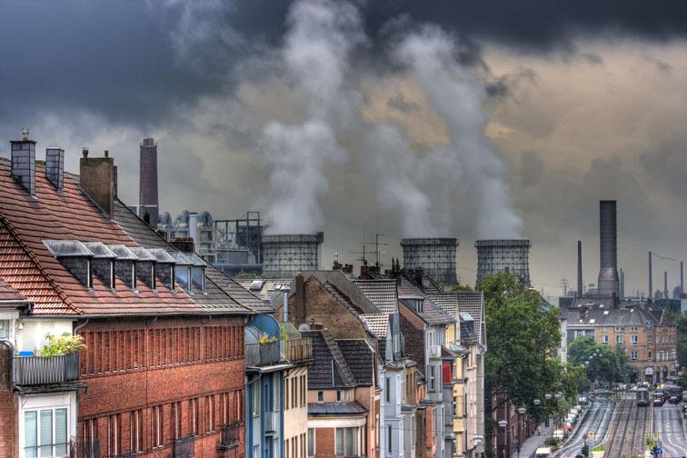 Schöne Bausubstanz im Vordergrund, davor eine Allee mit Straßenbahnschienen, im Hintergrund rauchende Industrieschlote; Detektive der Kurtz Detektei Düsseldorf