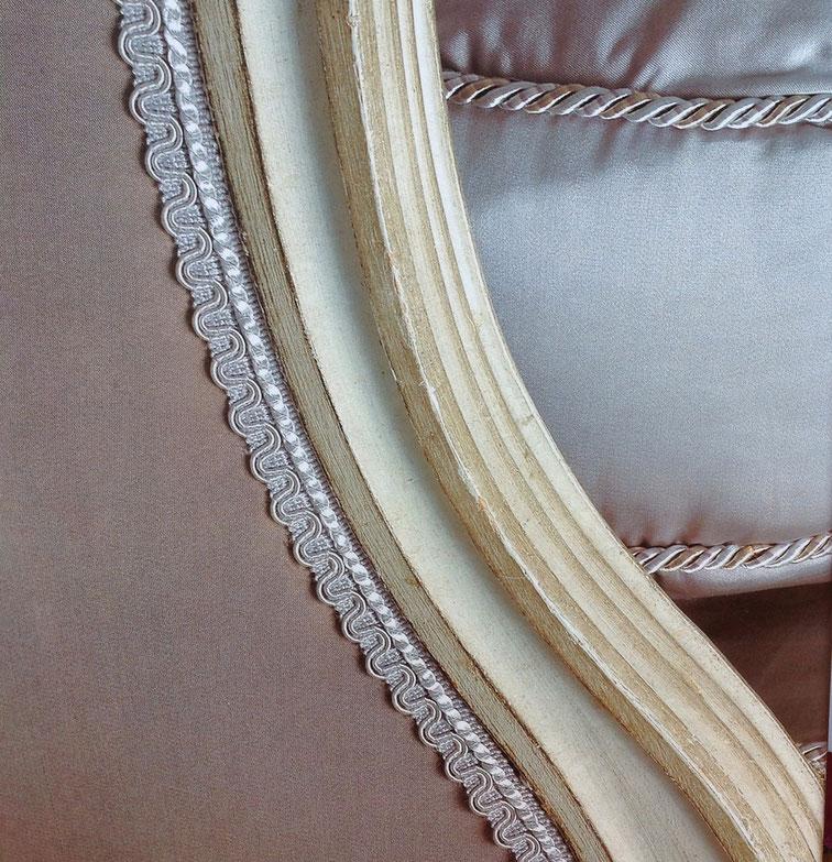 Détail de passementerie: une lézarde, galon dentelé en tissu, grise, orne le pourtour d'une bergère Louis XVI en satin gris. Photo de chez Houlès.