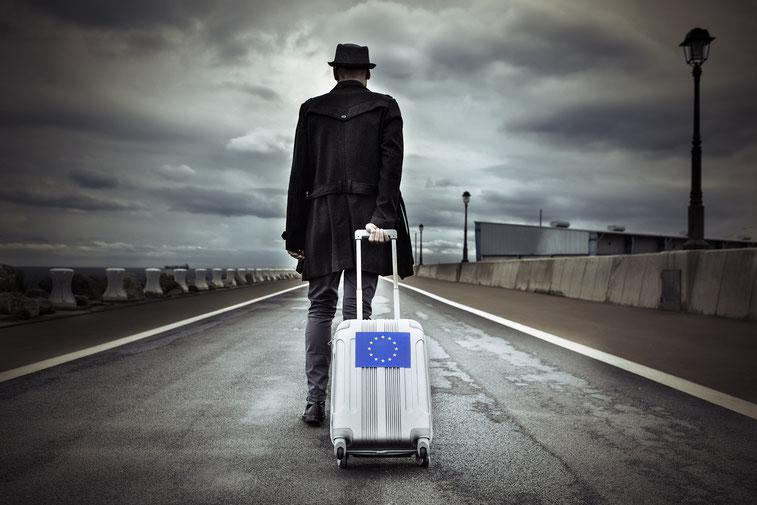 Mann läuft mit Rollkoffer bei bewölktem Himmel über eine Straße, Detektiv Bremen