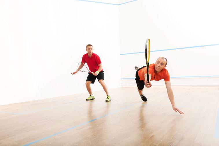 Zwei Männer spielen Squash, einer im Sprung; Kurtz Detektei Bochum