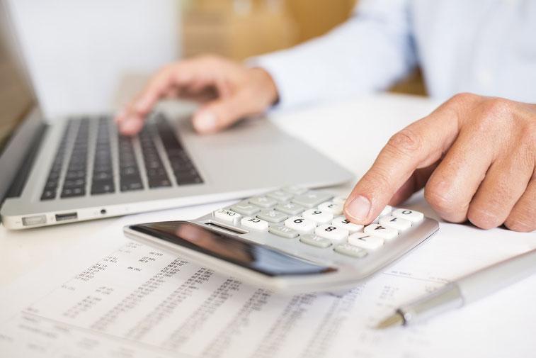 Mann tippt gleichzeitig auf einem Taschenrechner und auf einem Laptop, unter beiden liegt ein Bescheid mit Zahlen; Detektiv-Kosten Nürnberg, Franken, Bayern, Oberpfalz