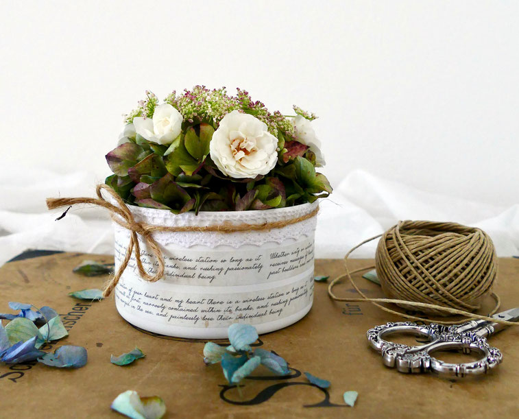 Weisse beschriftete Dose gefüllt mit Hortensien und weissen Rosen