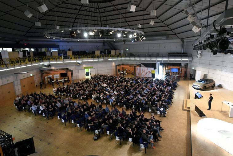 welcome-net Stuttgart, Eventagentur, Gäste im Plenum, Redner auf Bühne im Mercedes Event Center, Führungskräfte-Veranstaltung, Jahresabschluss