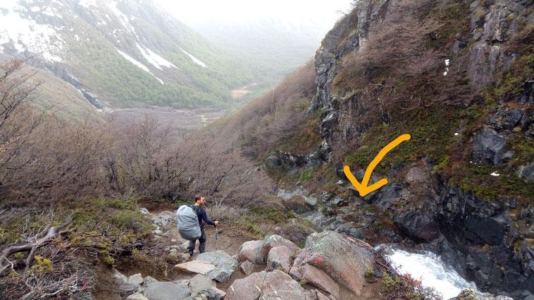 Jérôme est devant une cascade sur le flan de la montagne et cherche le chemin pour la traverser. On voit un peu la montagne enneigée au fond!