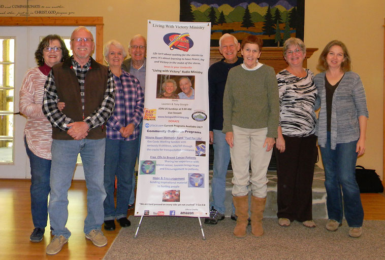 From Left: Jan and Jack Bazner, Judy and Dewey Gidcumb, Gerry and Cheryl Cline, Laura Bell and Holy Turner. They are standing around a poster for Living with Victory, a radio ministry that Mountain Top Experience supports.