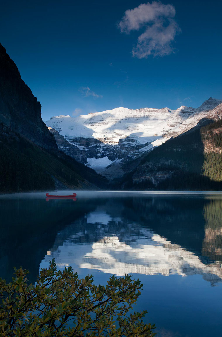 Red canoe on Lake Louise with mountains and sunshine, Banff National Park, Alberta, Canada, 1200x1820px