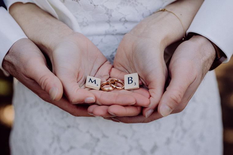 Hände des Brautpaares halten die goldfarbenen Eheringe