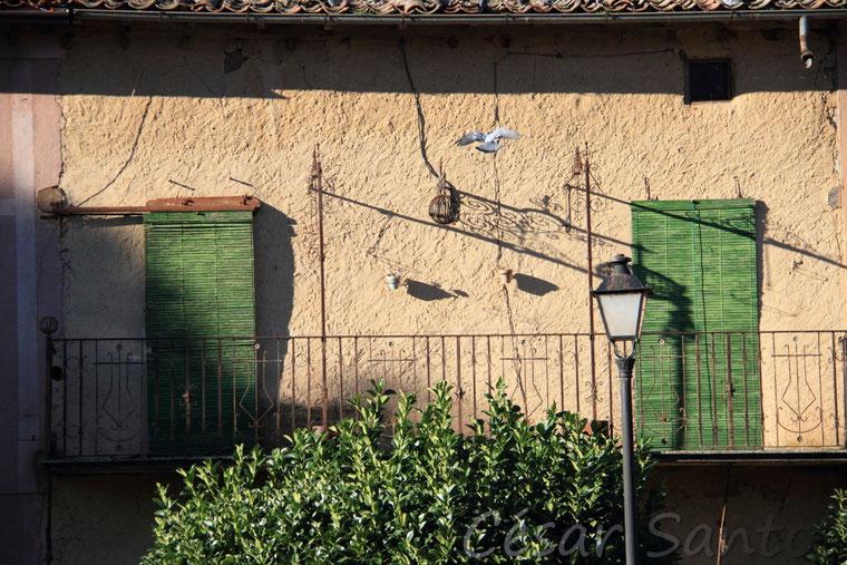 Amanecer, fachada de casa, ventanas, persianas verdes, farola