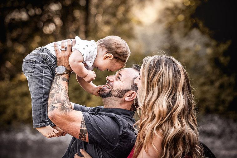 Familien Fotografie Vater hält Sohn hoch und Mutter schaut zu in Szene gesetzt von der Familien Fotografin Monkeyjolie in Appenzell