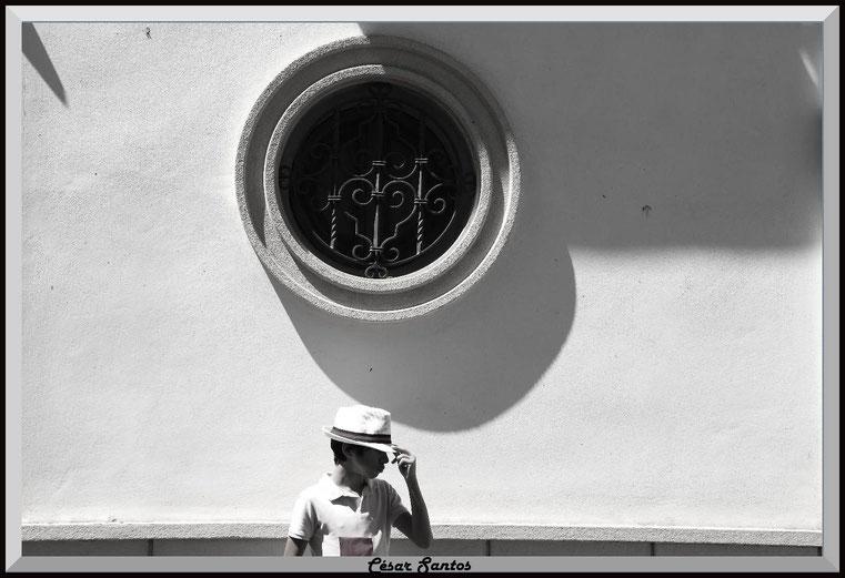 Niño con sombrero posando ante una fachada. Ventana redonda