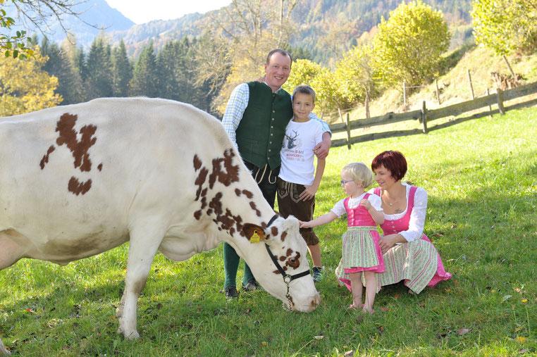 Auf dem Bild sieht man die Familie Danklmaier, Silke, Martin, Jonathan und Maya mit einer Kuh aus ihrer Holsteinzucht auf der Weide