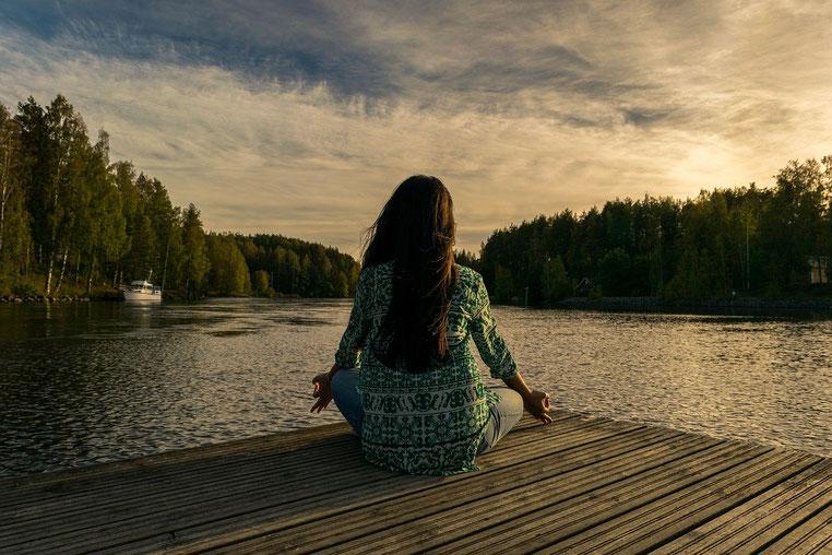 Femme brune aux cheveux longs, portant une tunique, qui médite assise en tailleurs sur un ponton. Elle est face à un lac.