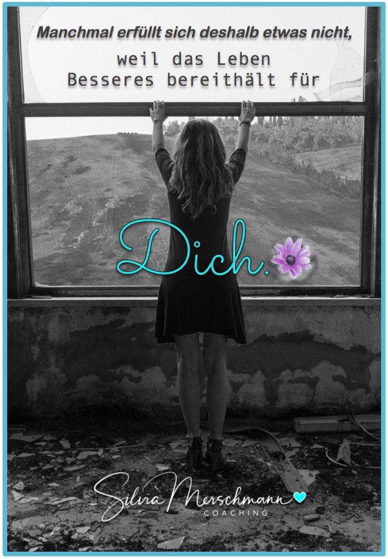 Frau steht vor einem Fenster und schaut in die Landschaft. Bild mit Text.