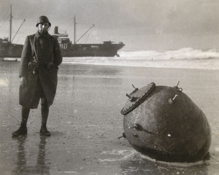 Dutch soldier with a Seamine, at the background SS Jeanette, Vlieland 1939.