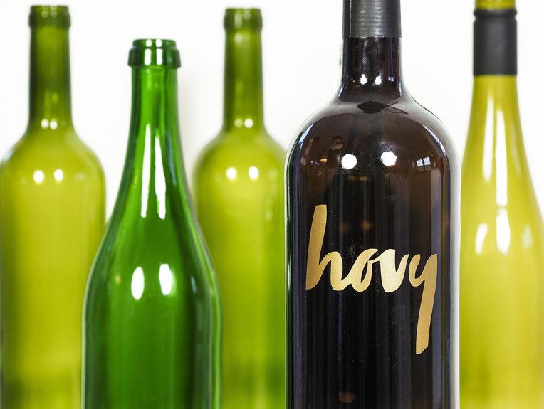 Leere Weinflaschen, eine mit goldenem HOVY-Schriftzug im Vordergrund