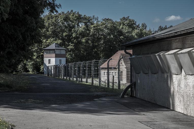 """Wachturm mit Stacheldrahtzaun und der Arrestzelle """"Bunker"""" - einer Mord- und Folterstätte des Lagers"""