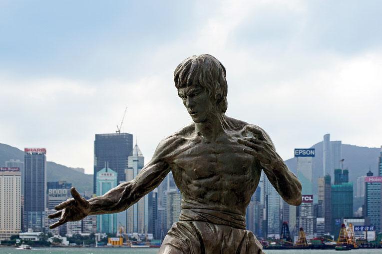 Die Statue von Bruce Lee im Hafen von Hongkong. Im Hintergrund sieht man die Skyline von Hongkong