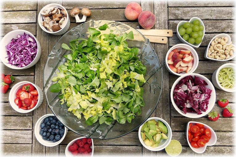 Es stehen viele rohköstliche Salate auf einem Tisch wie grüner Salat, Tomaten, Erdbeeren, Weintrauben, Pfirsiche, Nüsse