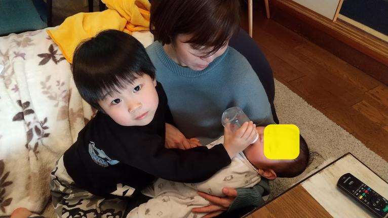 赤ちゃんにミルクをあげる次男の写真