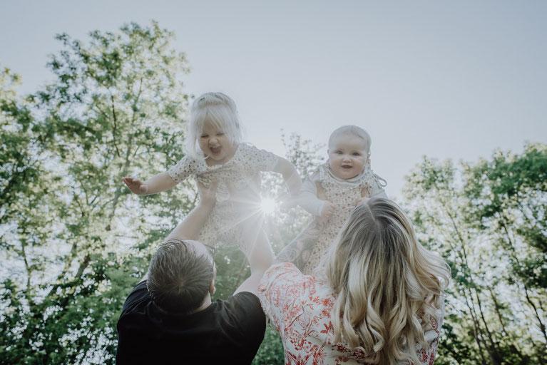 Junge Eltern werfen ihre beiden kleinen Mädchen bei Gegenlicht in die Luft fotografiert von Familienfotografin Uschi Kitschke aus Kreuzau.