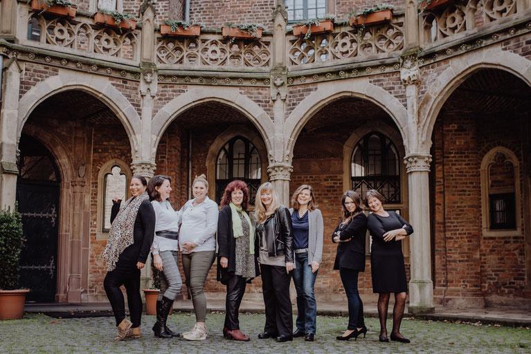 Gruppenfoto von acht Frauen vor den Säulen vom Schloß Paffendorf locker in einer Reihe aufgestellt mit Blick in die Kamera zu, fotografiert von Portraitfotografin Uschi Kitschke aus Kreuzau.