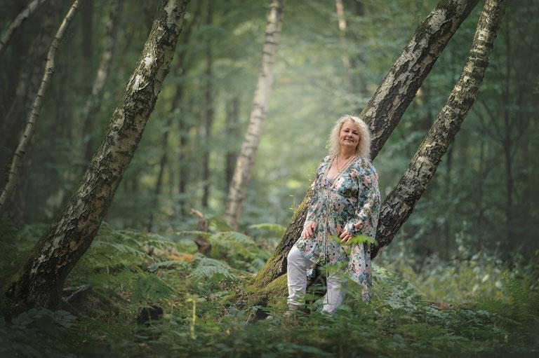 Pianistin Hauke Kranz im Wald, an eine Birke gelehnt