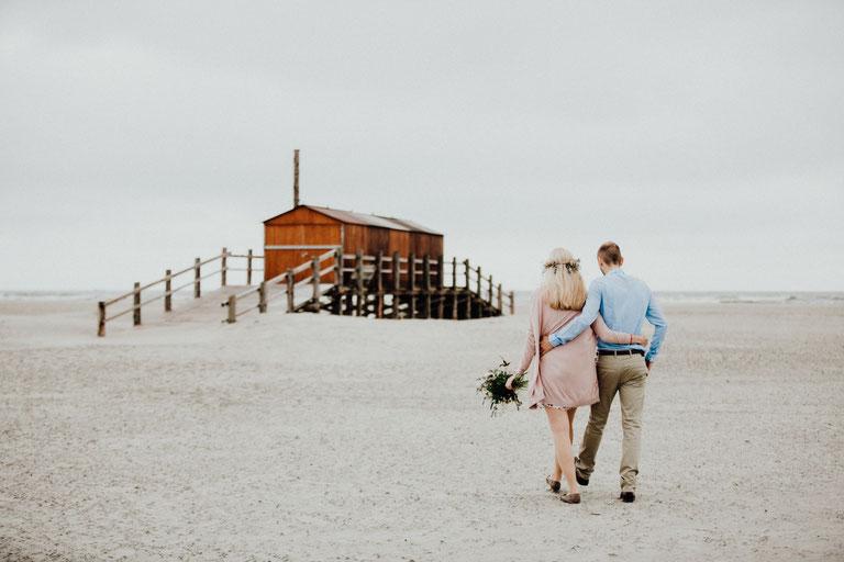 Paarfotograf am schönen Strand von Sankt Peter Ording zwischen Pfahlbauten.