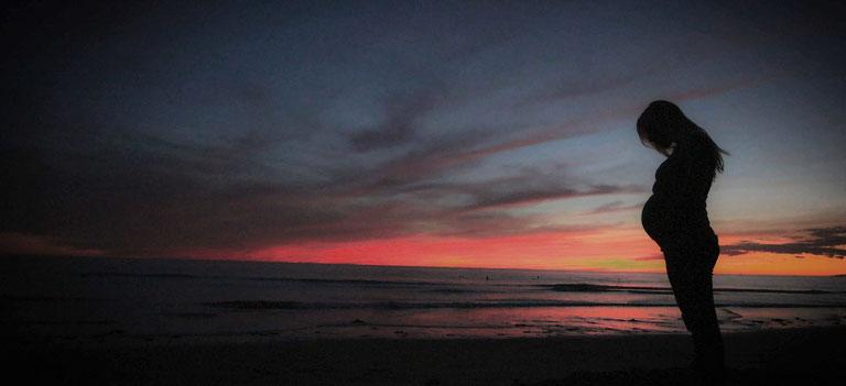 Mujer embarazada en playa en el atardecer
