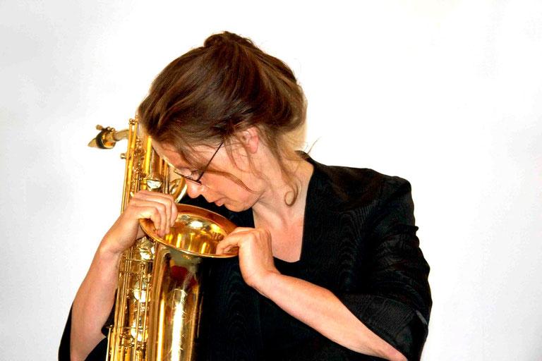 Anne Wiemann sieht von oben in den golden leuchtenden Trichter eines Bariton Saxofons