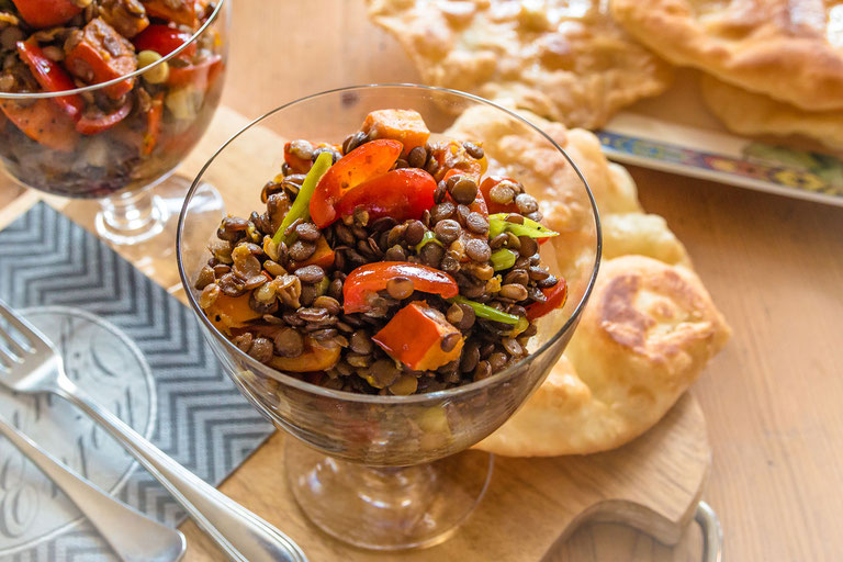 Köstlicher Kürbis-Linsensalat serviert in Glasschale mit Naan als Beilage - Rezept