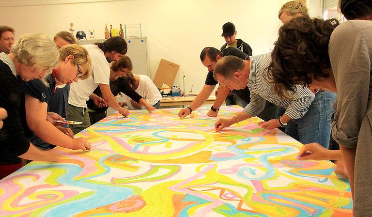 Mitarbeiter einer Einrichtung arbeiten gemeinsam an einem Kunstwerk