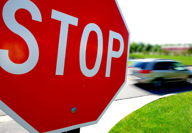 Car Speeding Through Stop Sign Intersection