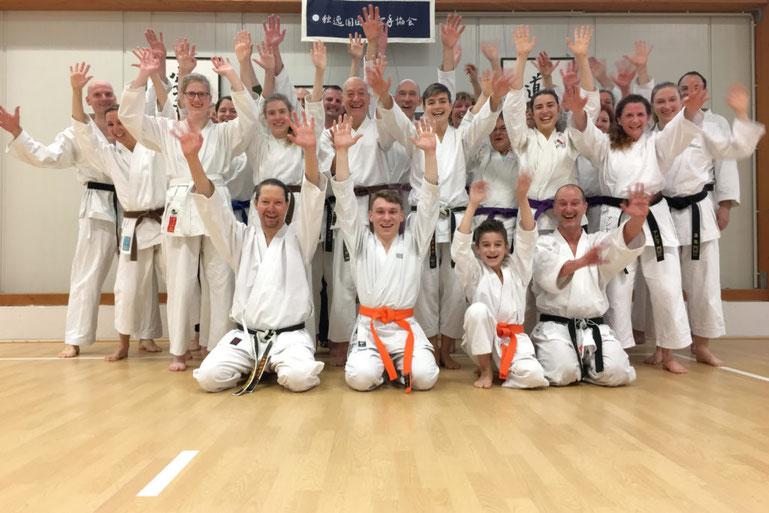 Karate-Schüler machen ein Gruppenfoto und freuen sich über bestandene Prüfungen.