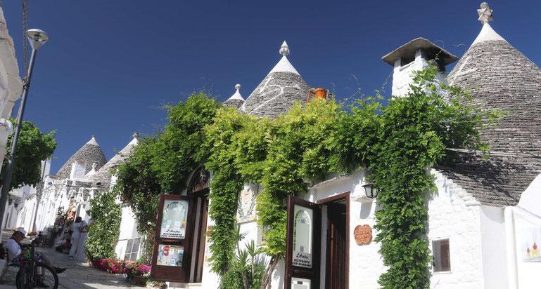 Typische Trulli-Häuser grün bewachsen mit blauem Himmel in Alberobello