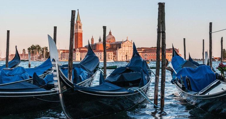 Gondeln in Venedig im sanften Licht mit der Stadt im Hintergrund