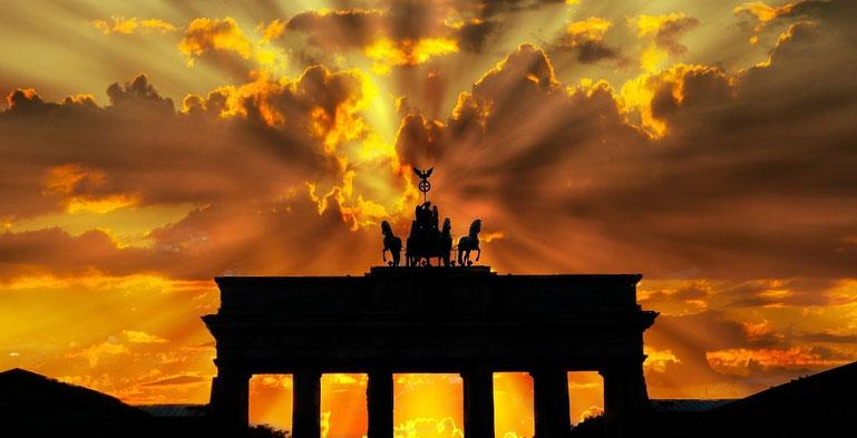 Brandenburger Tor scherenschnittartig hinterleuchtet vom dramatischen Abendlicht