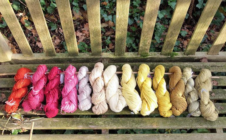 Strangwolle handgefärbt mit Naturfarben in verschiedenen Farbtönen und Wollqualitäten auf einer alten Gartenbank