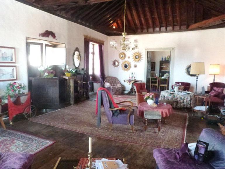 Wohnzimmer mit offenem Kamin und einer antiken Holzdecke, sehr geräumig gebaut.