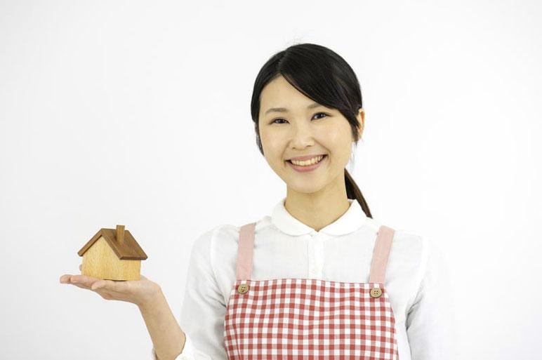 家の模型を手に乗せほほ笑む女性