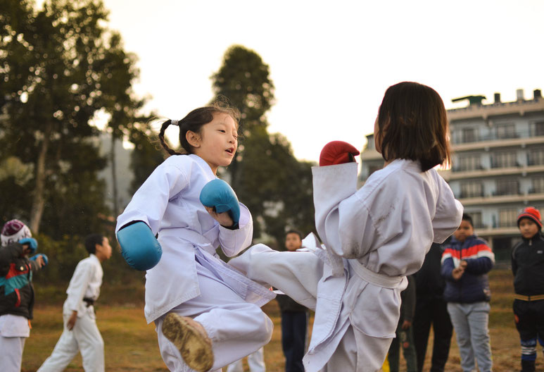 Zwei Kinder trainieren Karate. Das Mädchen mit den roten Boxhandschuhen tritt das Mädchen mit den blauen Boxhandschuhen.