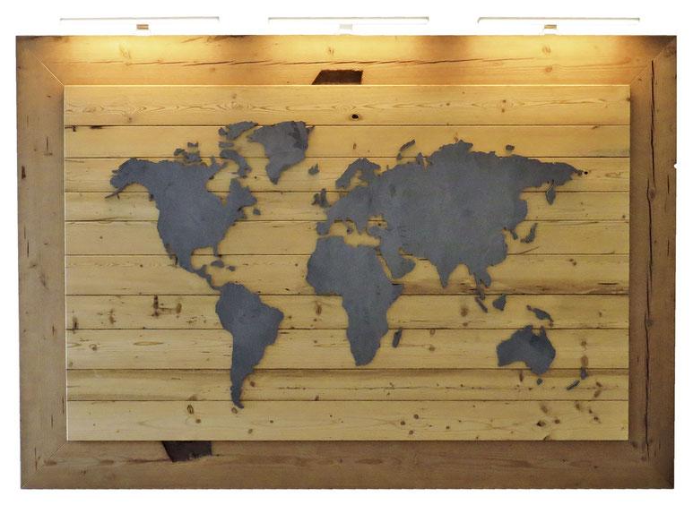 Weltkarte aus Stahl, Träger und Umrahmung aus Altholz, von oben beleuchtet durch drei Bilderleuchten
