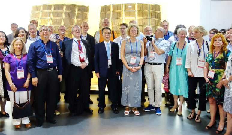 The museum's head curator, Dr Jeong-Ha Hwang, with the International Association of Printing Museum delegates standing before the Jikji display.