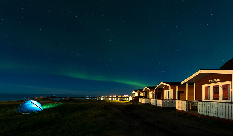 Illuminated tent and wooden cabins at Ramberg beach, Lofoten Islands, Norway, Scandinavia, Europe