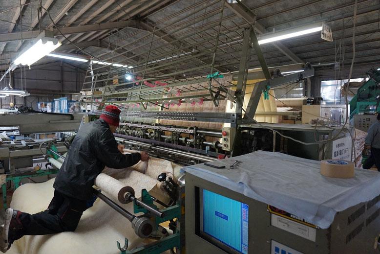 多針キルト機を使って表裏の生地とウール綿を糸で縫い合わせます。