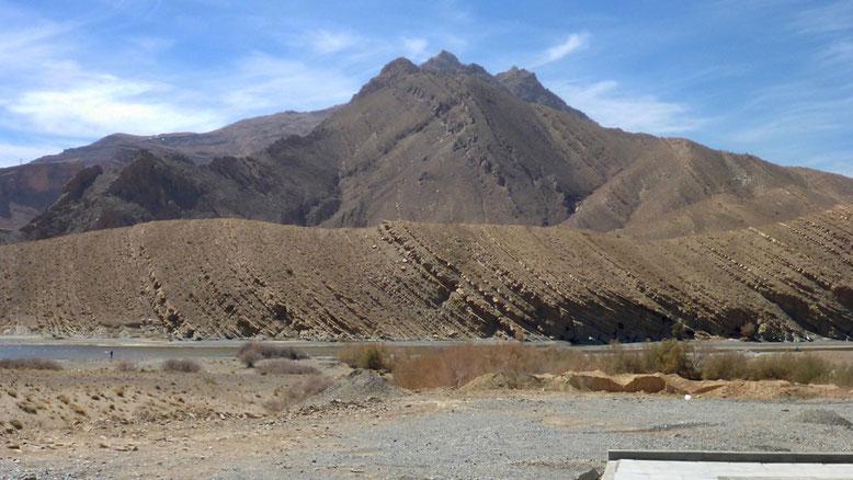 Ursprünglich horizontal abgelagerte Sedimentpakete fallen zum rechten Bildrand ein. Wenn man genau hinsieht erkennt man, dass dies auch für das Bergmassiv im Bildhintergrund gilt.