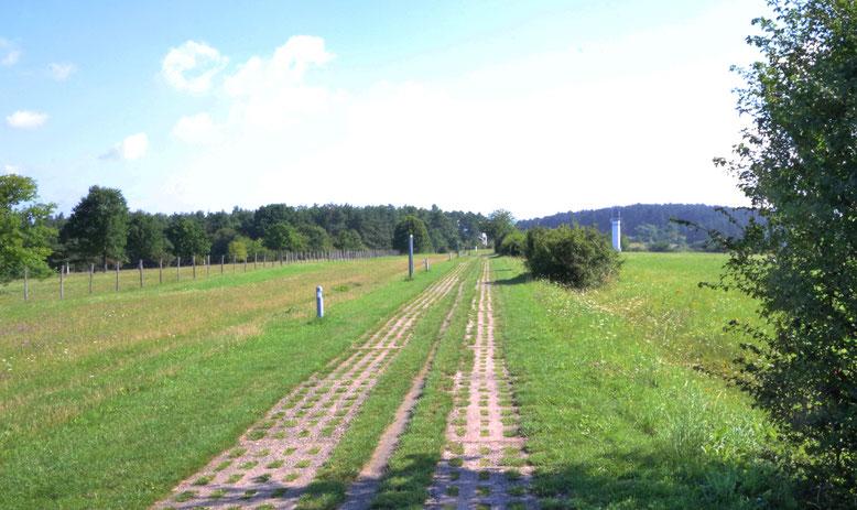 Ehemaliger Kolonnenweg mit DDR-Grenzturm, rechts hinten im Bild. In gerader Verlänge-rung des Kolonnenweges ist der amerikanische Kontrollturm eben noch zu erahnen.
