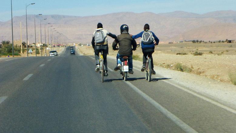 Kurz vor Errachidia nutzen zwei Radfahrer die Pferdestärken ihres mopedfahrenden Kumpels. Vor 50 Jahren auch bei uns eine gerne in Anspruch genommene Unterstützung. Heute in Europa fast undenkbar ohne dass die Ordnungsmacht sofort einschreitet.